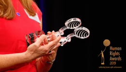 Woman holding two human rights trophies